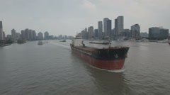 Flying in front of a cargo vessel on the Huangpu river in Shanghai Stock Footage