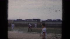 1964: handsome young boys in uniforms playing a game of baseball on the field Stock Footage