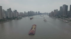 Flying over vessels sailing past tall skyscrapers in Shanghai Stock Footage