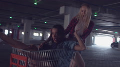 Girls having fun at the shopping mall, spinning each other in shopping cart Stock Footage