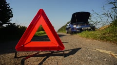 Hazard warning triangle by broken down car on country road uk Stock Footage