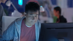 4K Close up portrait young Asian computer game designer working at his desk Stock Footage