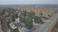 Aerial flight over new suburban apartment buildings and construction site China Stock Footage