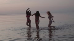 Group of Three Teenage Girls Dancing In The Water At The Beach At Sunset in Slow Stock Footage