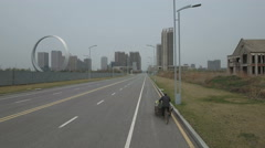 Tracking a lonely garbage collector on bicycle in ghost city China Stock Footage