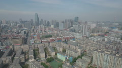 Aerial drone flight over residential buildings towards skyline Shenyang China Stock Footage
