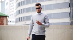 Young man with sunglasses and bag walking in city Stock Footage