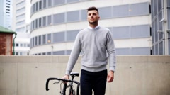 Young man walking along city street with bicycle Stock Footage