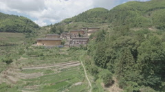 Flying over rice terraces towards classic tulou round houses in China Stock Footage