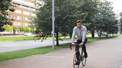 Young man riding bicycle on city street Stock Footage