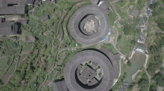Flying over rural landscape and Fujian tulou round houses in China Stock Footage