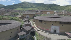 Rise up aerial shot of classic Fujian tulou round houses in China Stock Footage