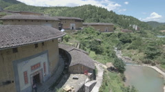 Flying over classic tulou round houses in Fujian, China Stock Footage