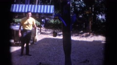 1966: man watches bird play with bucket FLORIDA Stock Footage