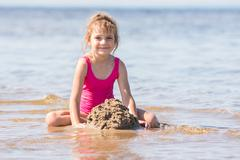 Five-year girl in a pink bathing suit playing in the sand in the shallows of  Stock Photos