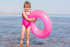 Five-year girl in a pink bathing suit standing with swimming laps in the rive Stock Photos