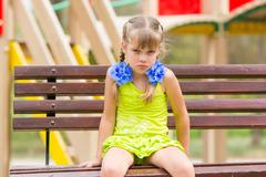 Offended five year old girl sitting on a bench at the playground Stock Photos