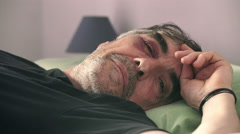 Man injured after a car accident lying on the bed looking at the camera Stock Footage