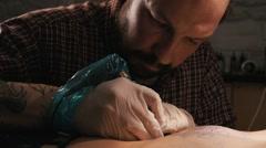 Tattoo master with beard making a tattoo of mandala pattern. Close up shot Stock Footage