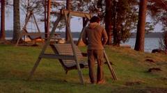 Alone man swinging on coast of lake and watching sunset Stock Footage