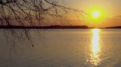 Sunset on the lake. Sunset reflected in water. Silhouettes of trees Stock Footage