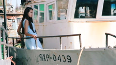 Young girl at the stern of the old vessel. Girl posing on board merchant ships Stock Footage