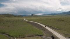 Aerial drone shot of Tibetan herdsman riding through green pastures Stock Footage