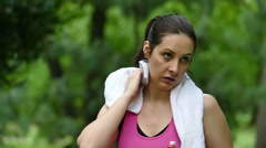 Young woman wipes sweat with a towel during a recreation Stock Footage