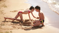 Children. boy and girl playing with sand on the beach. build a sand castle Stock Footage