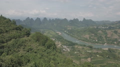 Flying over forest revealing small village in limestone mountain peaks China Stock Footage