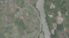 Overhead view of green paddy fields and river in rural China Stock Footage