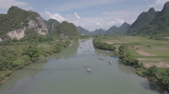 Drone shot bamboo rafts sailing through spectacular mountain scenery China Stock Footage