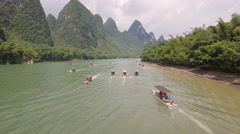 China tourism, aerial shot motorized rafts sailing through mountain landscape Stock Footage