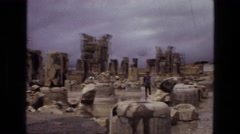 1972: people looking at ancient ruins while the ground is wet IRAN Stock Footage