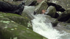 Flowing Creek in Slow Motion with Hiker's Resting Feet Stock Footage