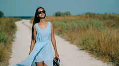 Slim girl goes by sandy road to the beach Stock Footage