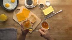 Man hands preparing breakfast toast with jam, top view Stock Footage