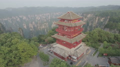 Flying over red Buddhist inspired pagoda building in Zhangjiajia mountains China Stock Footage