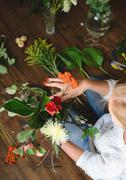Florist make a bouquet of flowers and branches Stock Photos