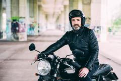 Mature male motorcyclist sitting on motorcycle wearing crash helmet under Stock Photos