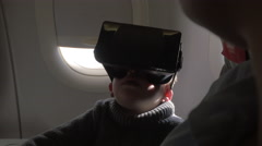 In plane sits a little boy with virtual reality glasses Stock Footage