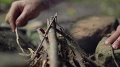 Male Camper Arranging Sticks on a Campfire in Slow Motion Stock Footage