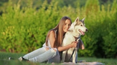 Attractive young woman hugs funny siberian husky dog Stock Footage