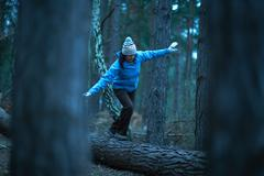 Female hiker balancing on fallen tree in forest Stock Photos
