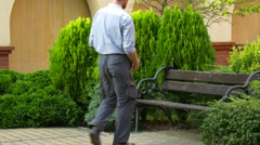 An Elderly Man Approaches to a Long Wooden Bench Stock Footage