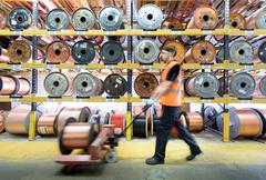 Worker with copper cable reels in cable factory Stock Photos