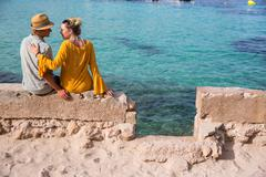 Rear view of couple sitting on wall by sea, Majorca, Spain Stock Photos