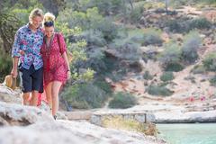 Couple strolling on rocks by sea, Majorca, Spain Stock Photos