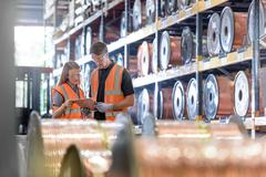 Workers with copper reels of cable in cable factory Stock Photos