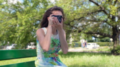 Pretty girl doing photos on old camera while sitting in the park Stock Footage